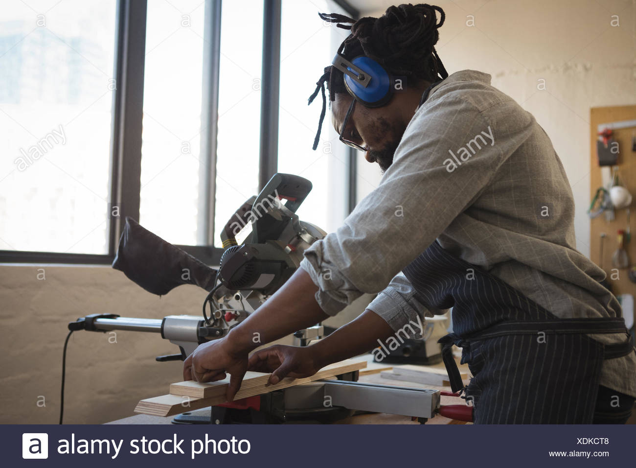 Carpenter cutting wooden plank with electric saw - Stock Image