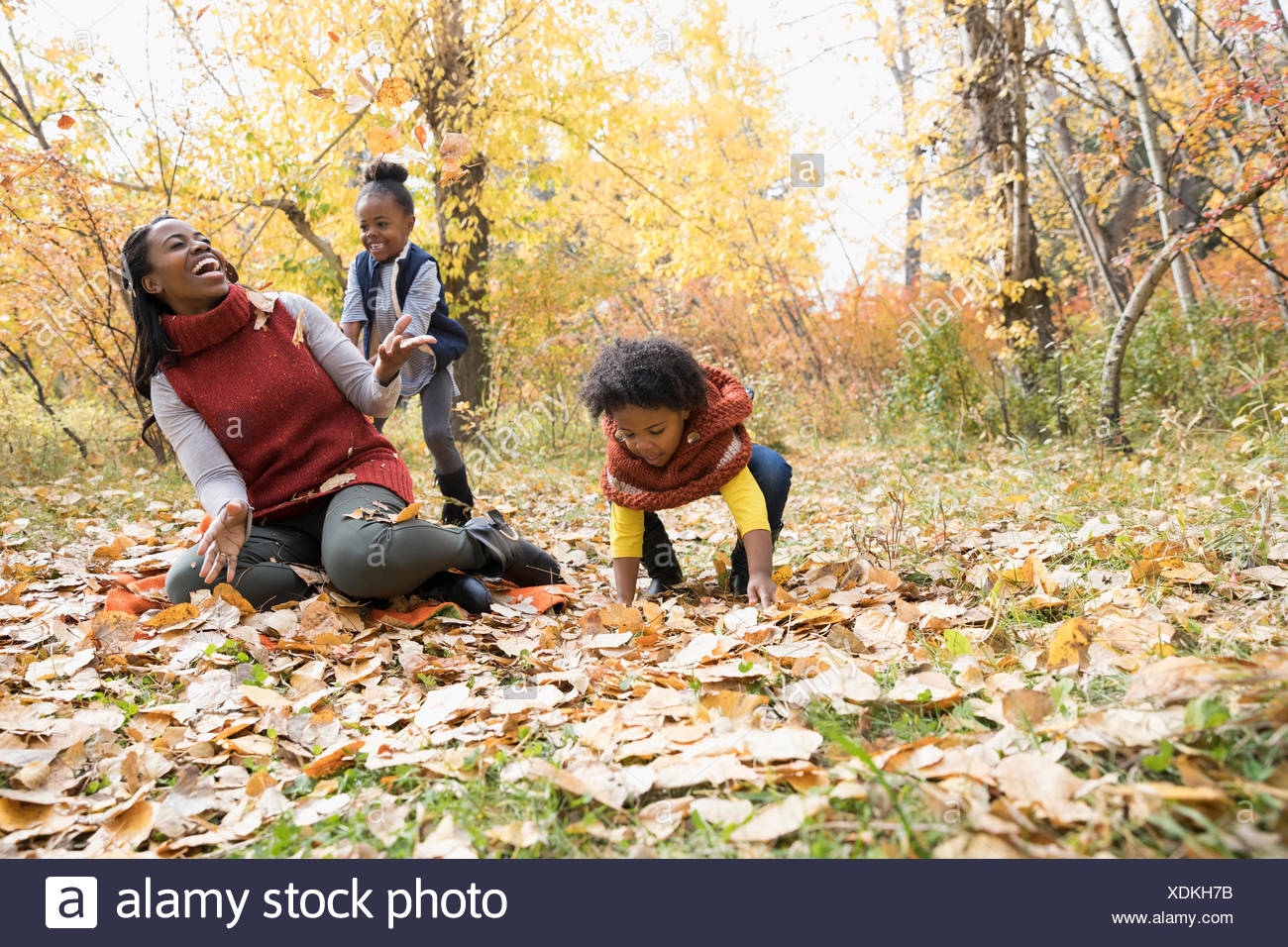 Mother and daughters playing throwing autumn leaves in park - Stock Image