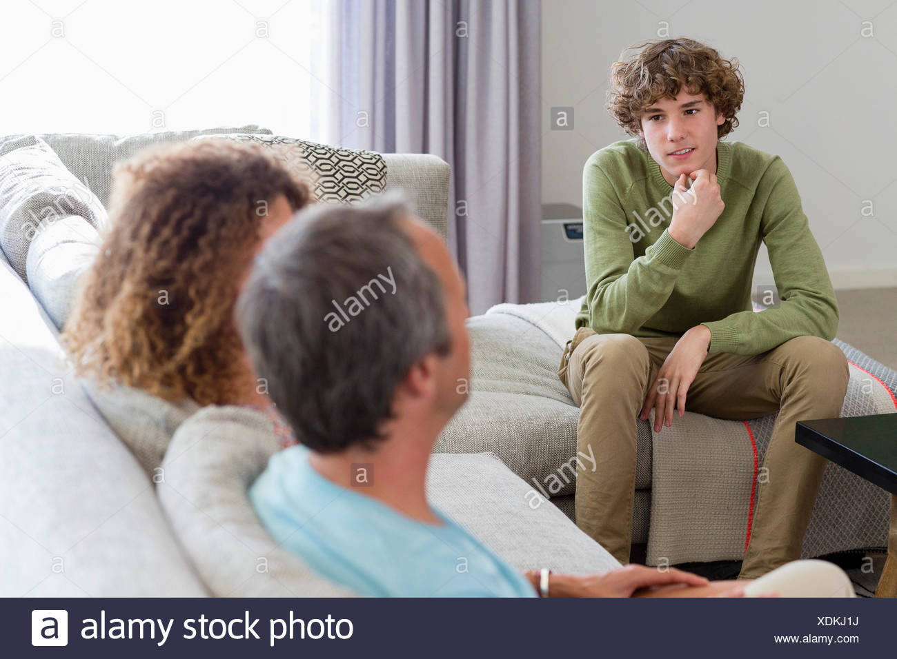 Happy family sitting in a living room at home - Stock Image