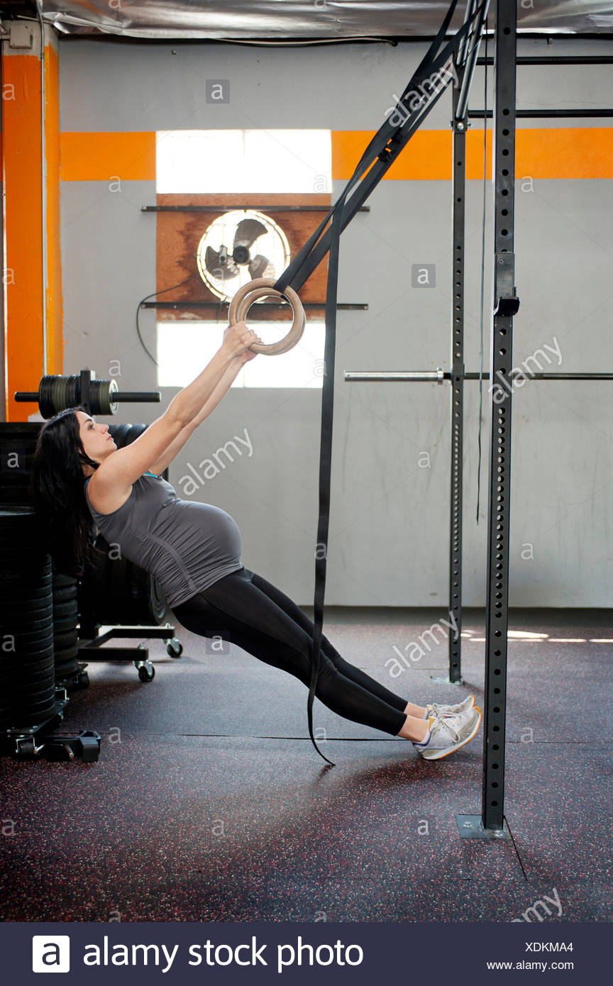 Pregnant young woman pulling gymnastic rings Stock Photo