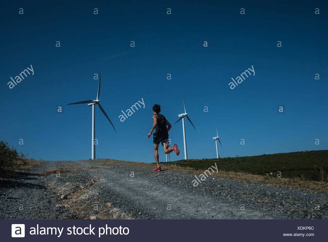 Mid adult man jogging on road, wind turbines in distance - Stock Image