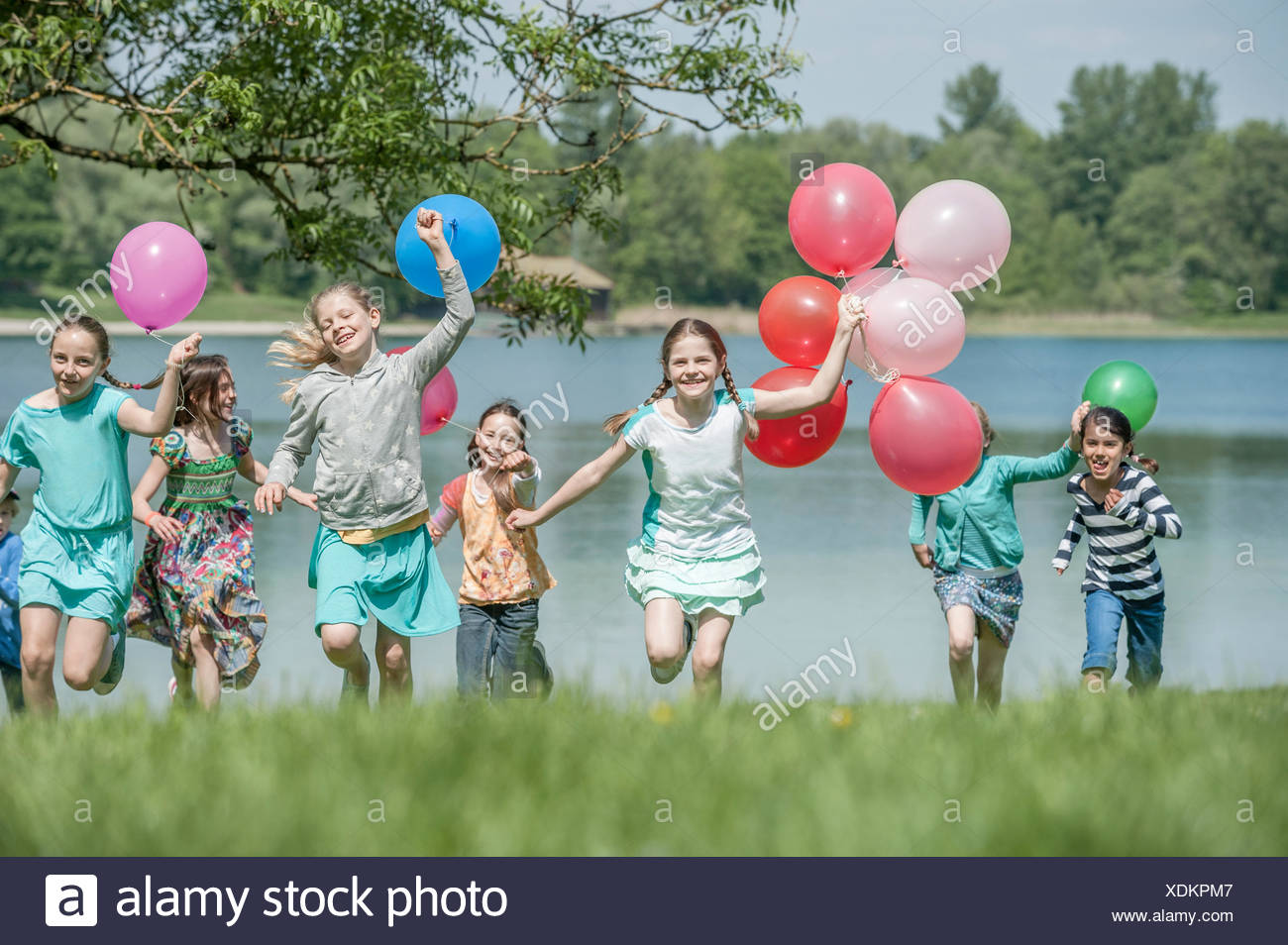 Children running in park with balloons, Munich, Bavaria, Germany - Stock Image
