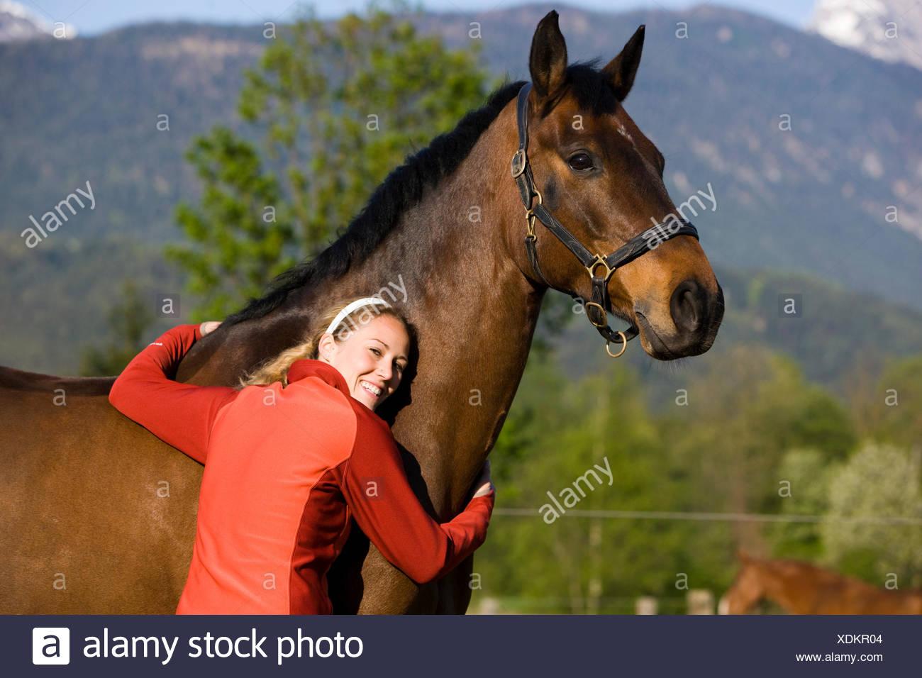 Young woman embracing an Austrian Warmblood, bay horse - Stock Image