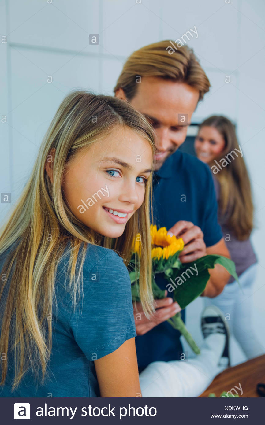 Smiling girl with parents at home - Stock Image