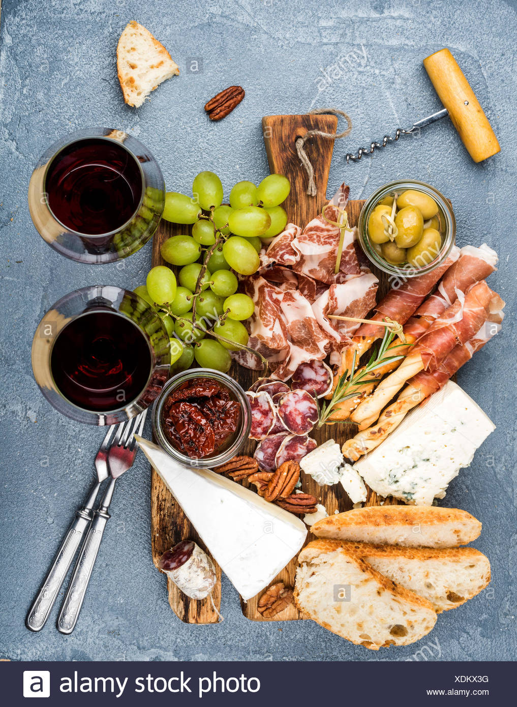 Cheese and meat appetizer selection. Prosciutto di Parma, salami, bread sticks, baguette slices, olives, sun-dried tomatoes, gra - Stock Image