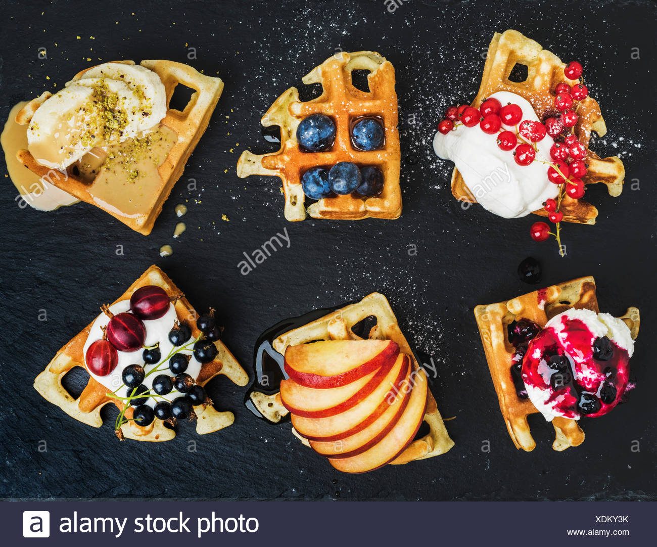 Warm belgian homemade waffles with fresh garden berries, fruit and ice cream on dark slate stone background, top view - Stock Image