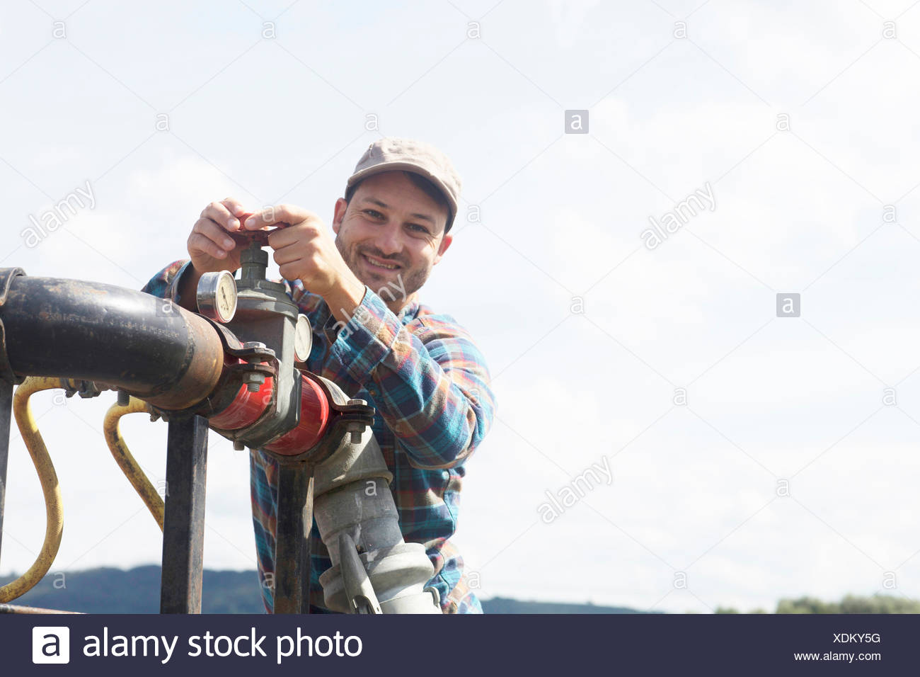 Man opening valve on industrial piping, looking at camera smiling - Stock Image