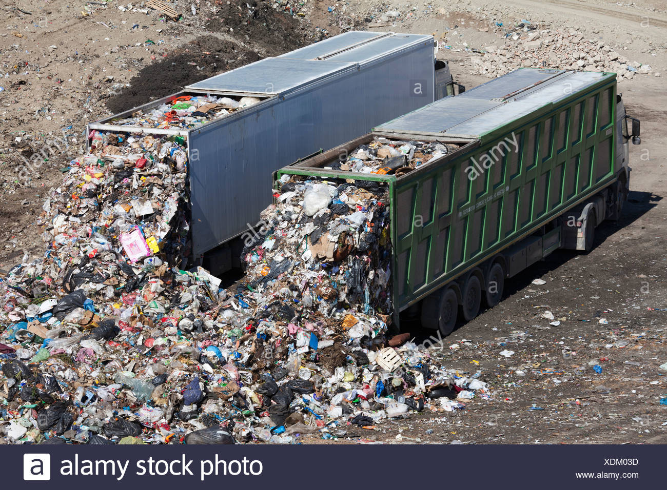 Trucks dumping waste in landfill - Stock Image