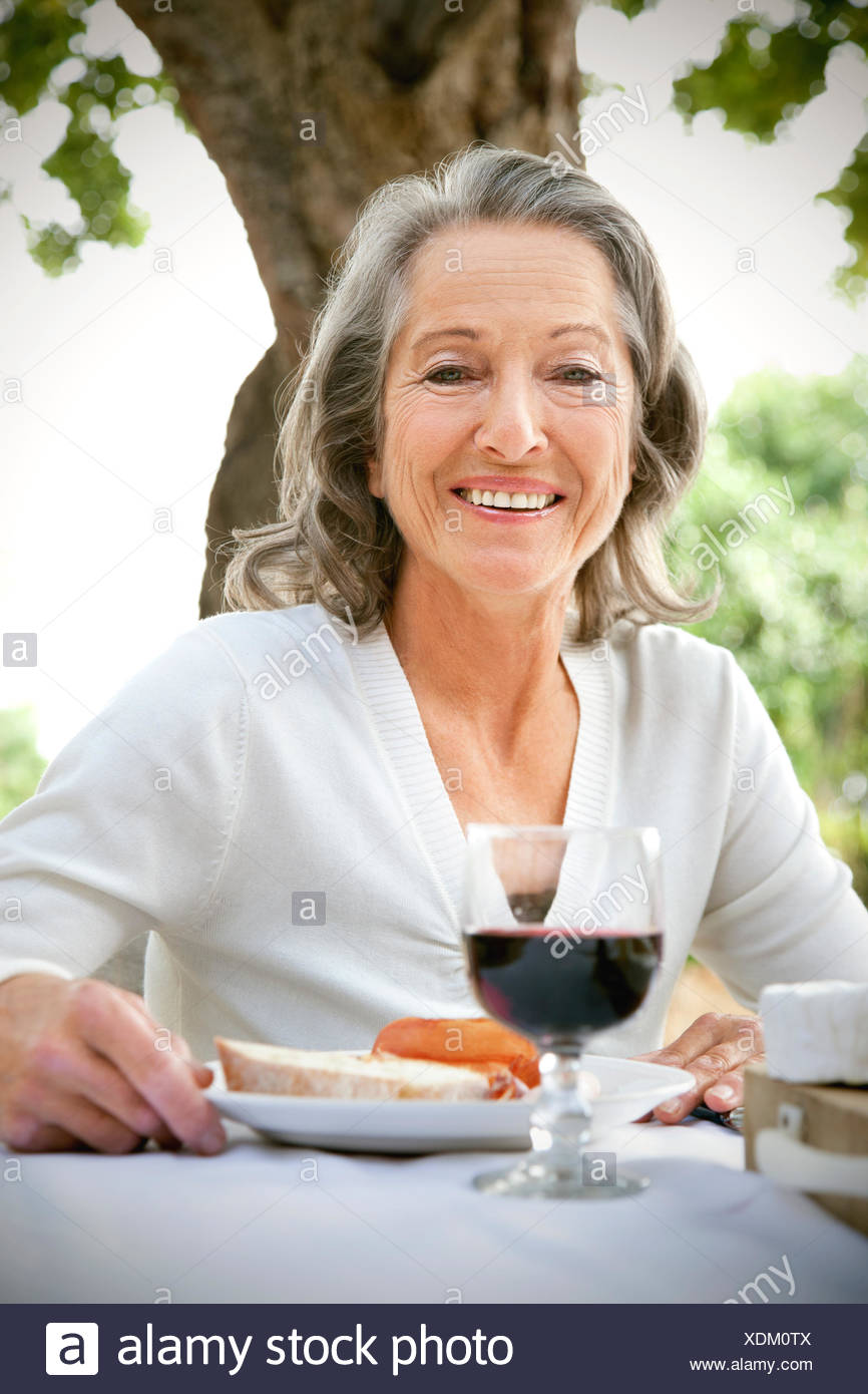 Portrait of smiling woman sitting at laid table in the garden - Stock Image