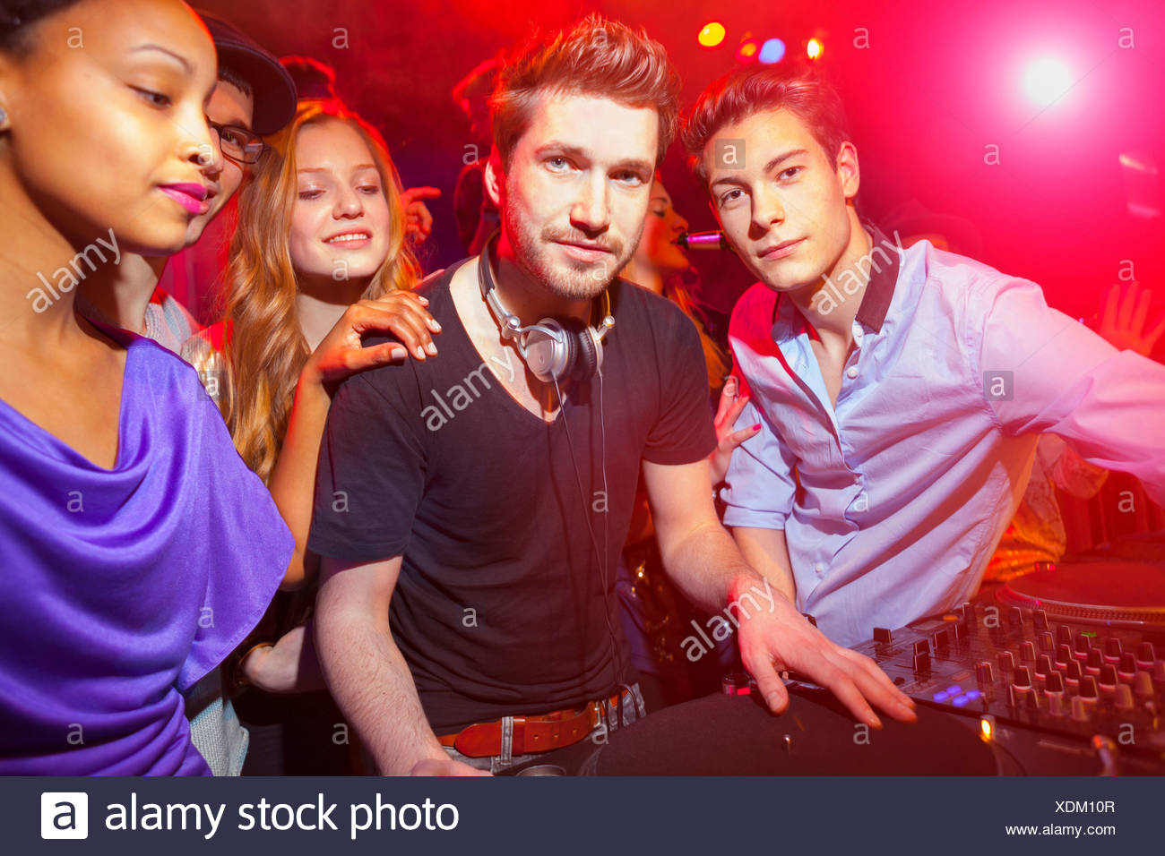 Disc Jockey surrounded by group of people - Stock Image