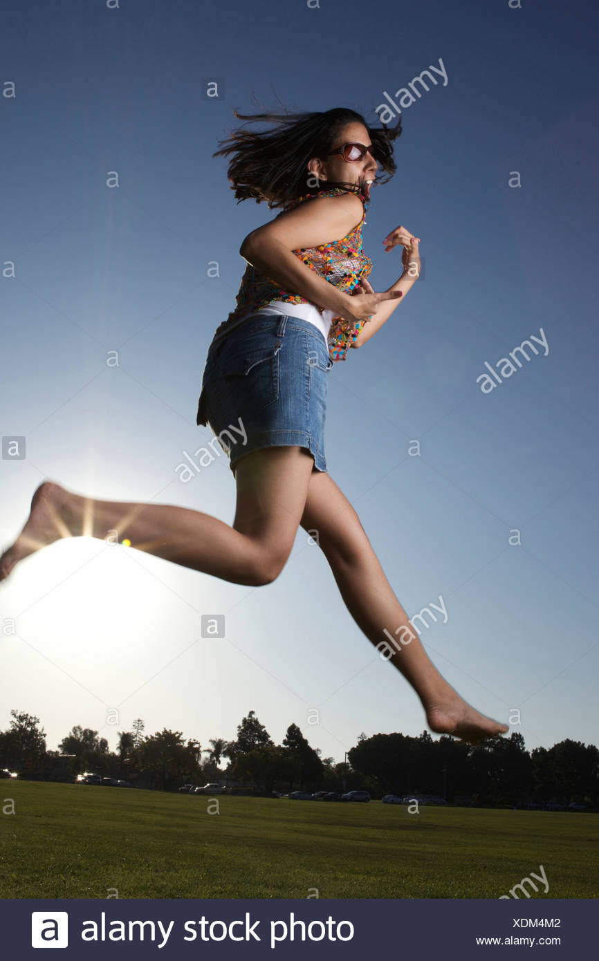 A happy woman dances in a sunny field. - Stock Image