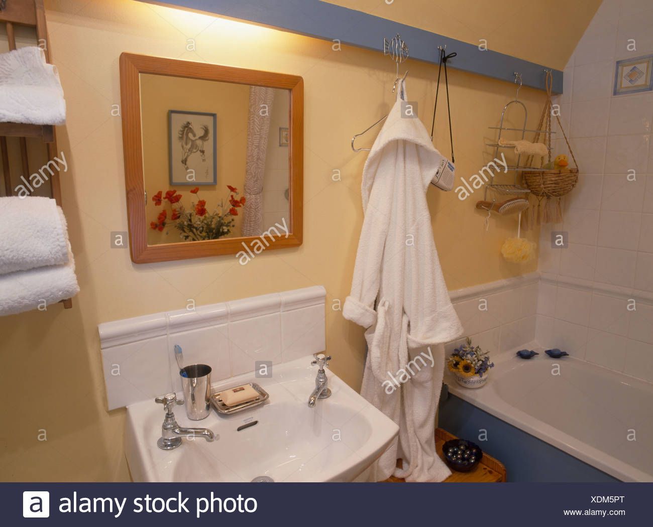 White bathrobe hanging on blue beam in yellow attic bathroom