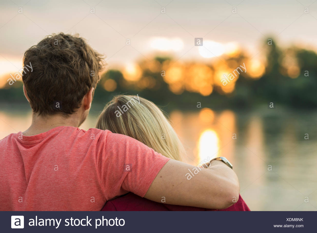 Young couple, man with arm around woman, rear view Stock Photo