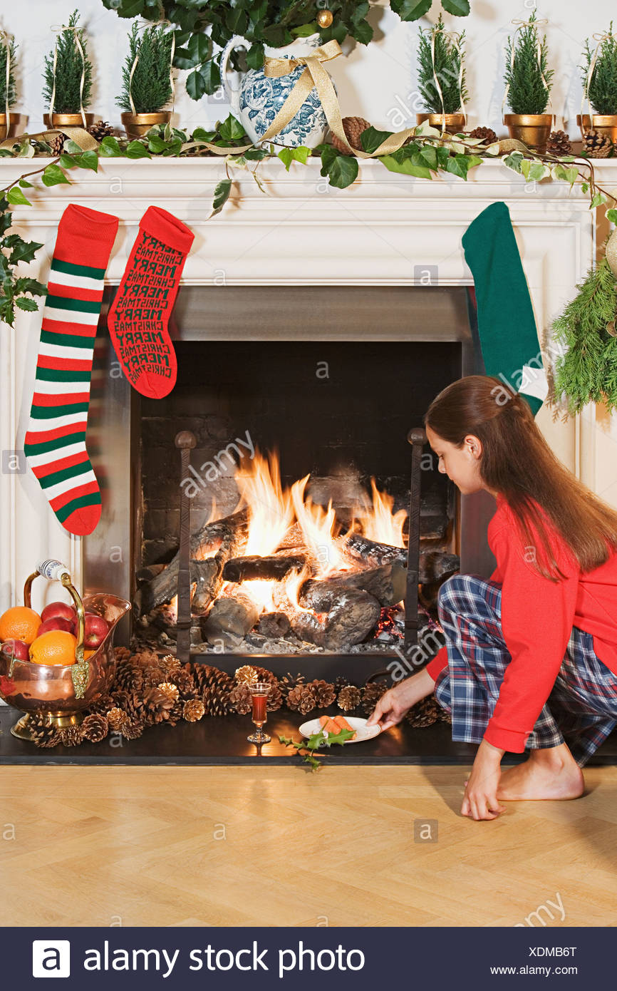 Girl placing festive items by fireplace - Stock Image