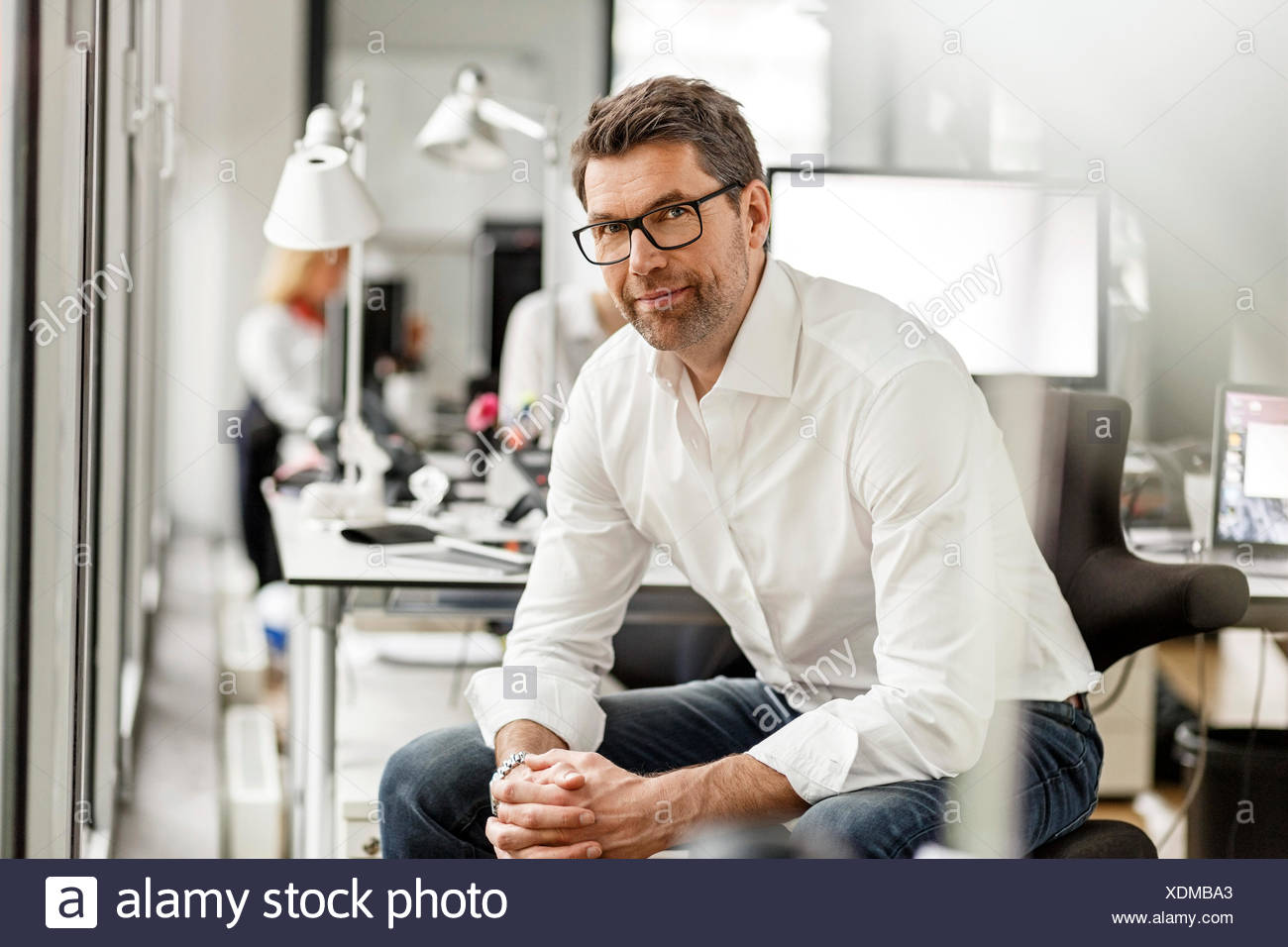 Portrait of businessman at desk in office - Stock Image