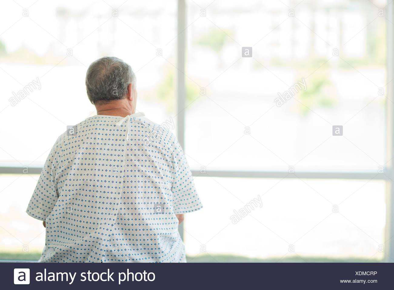 Male patient wearing gown looking through hospital window, rear view. - Stock Image
