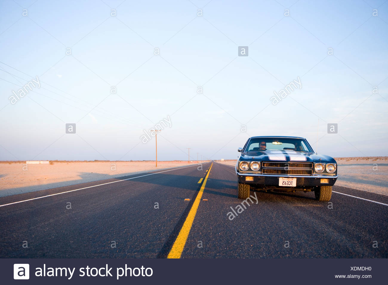 Classic car on freeway in desert, low angle view - Stock Image