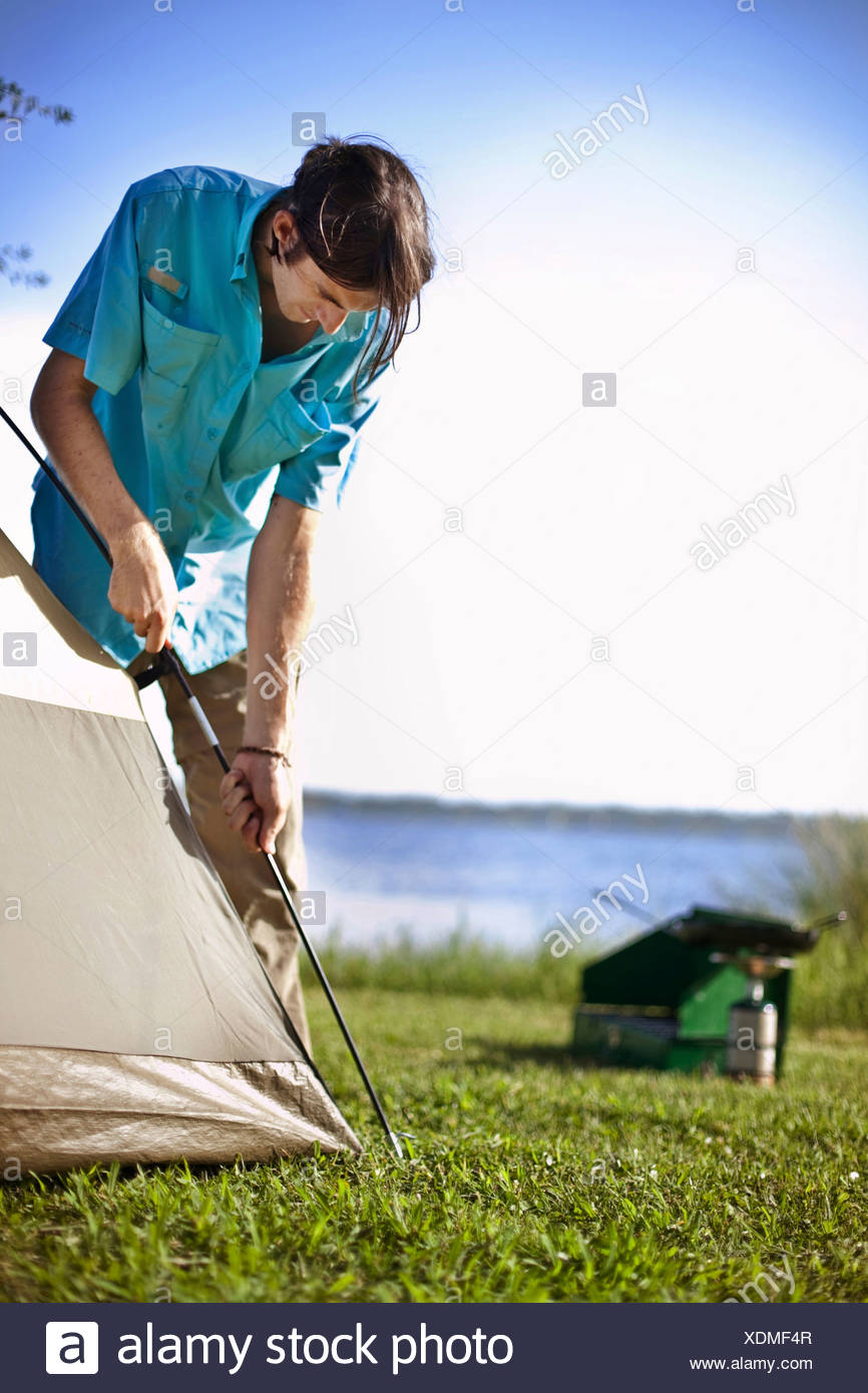 Young man assembles a tent on the banks of Shelby Lakes in Gulf Shores Alabama. Stock Photo