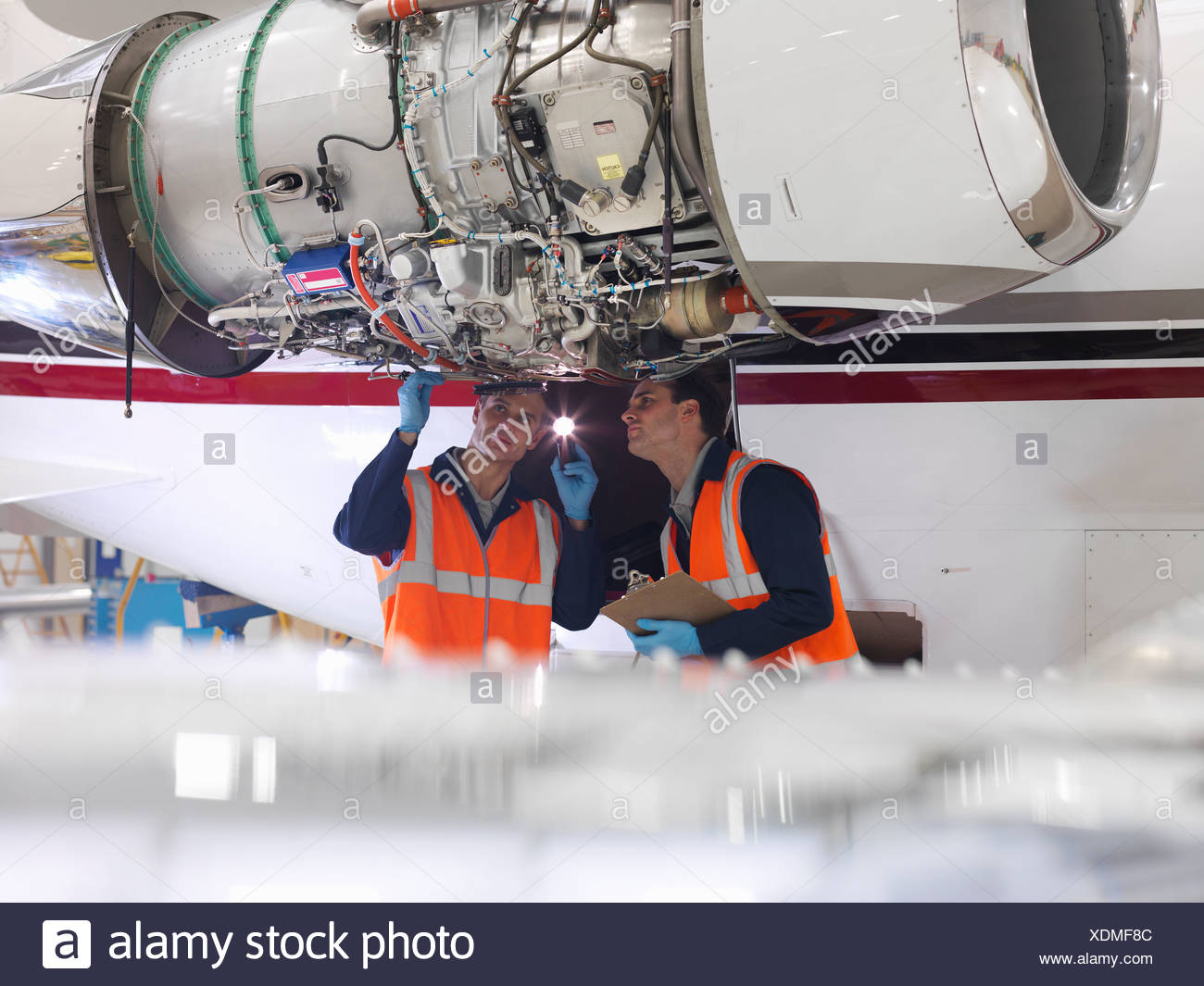 Engineers inspect a jet engine - Stock Image