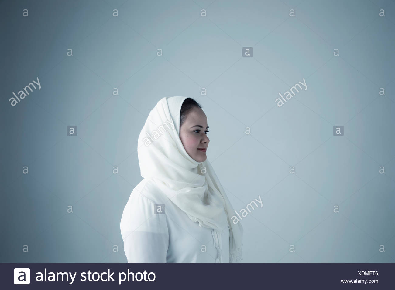 Portrait Middle Eastern young woman in white hijab and burka looking away - Stock Image