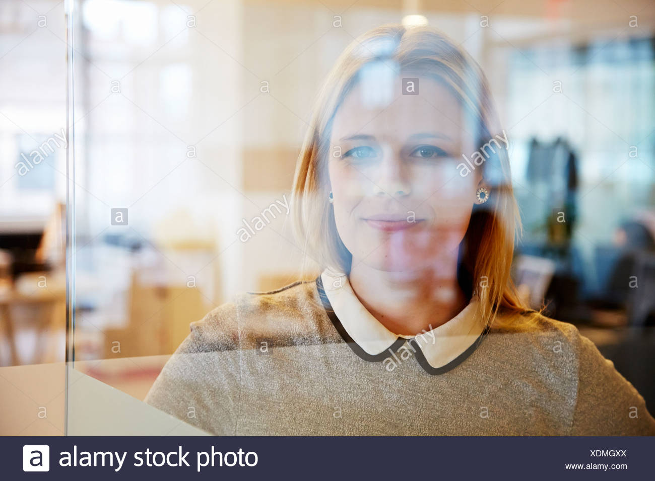 View through glass of female office worker - Stock Image