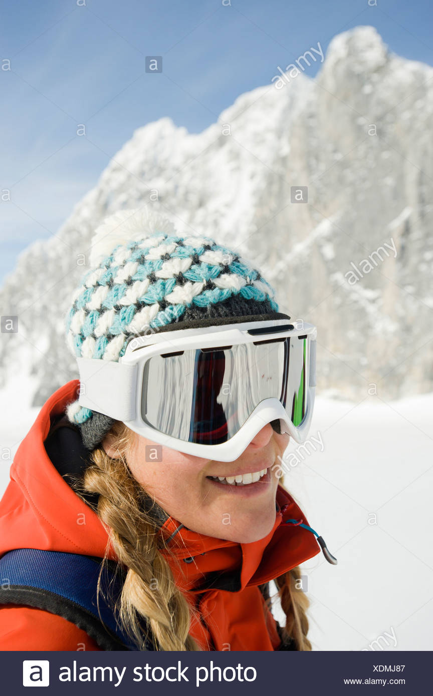 A young woman skier smiles at the camera in the backcountry of the Selkirk Mountains, Canada. - Stock Image