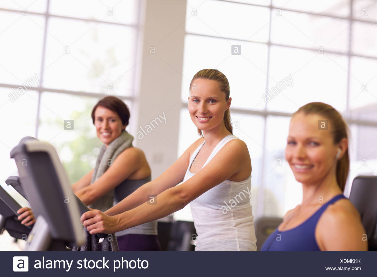 Portrait of smiling woman on exercise bike in gymnasium - Stock Image
