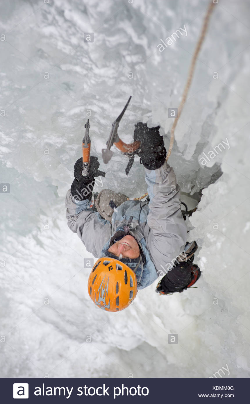 Ice climber climbs Ripple, a popular ice climb above the Eklutna River in the Chugach Mountains, Alaska - Stock Image