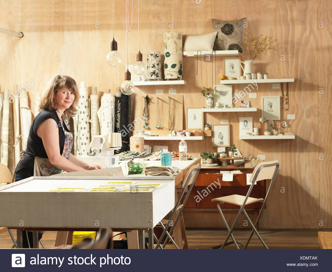 Woman at work table in hand-printing textile workshop - Stock Image