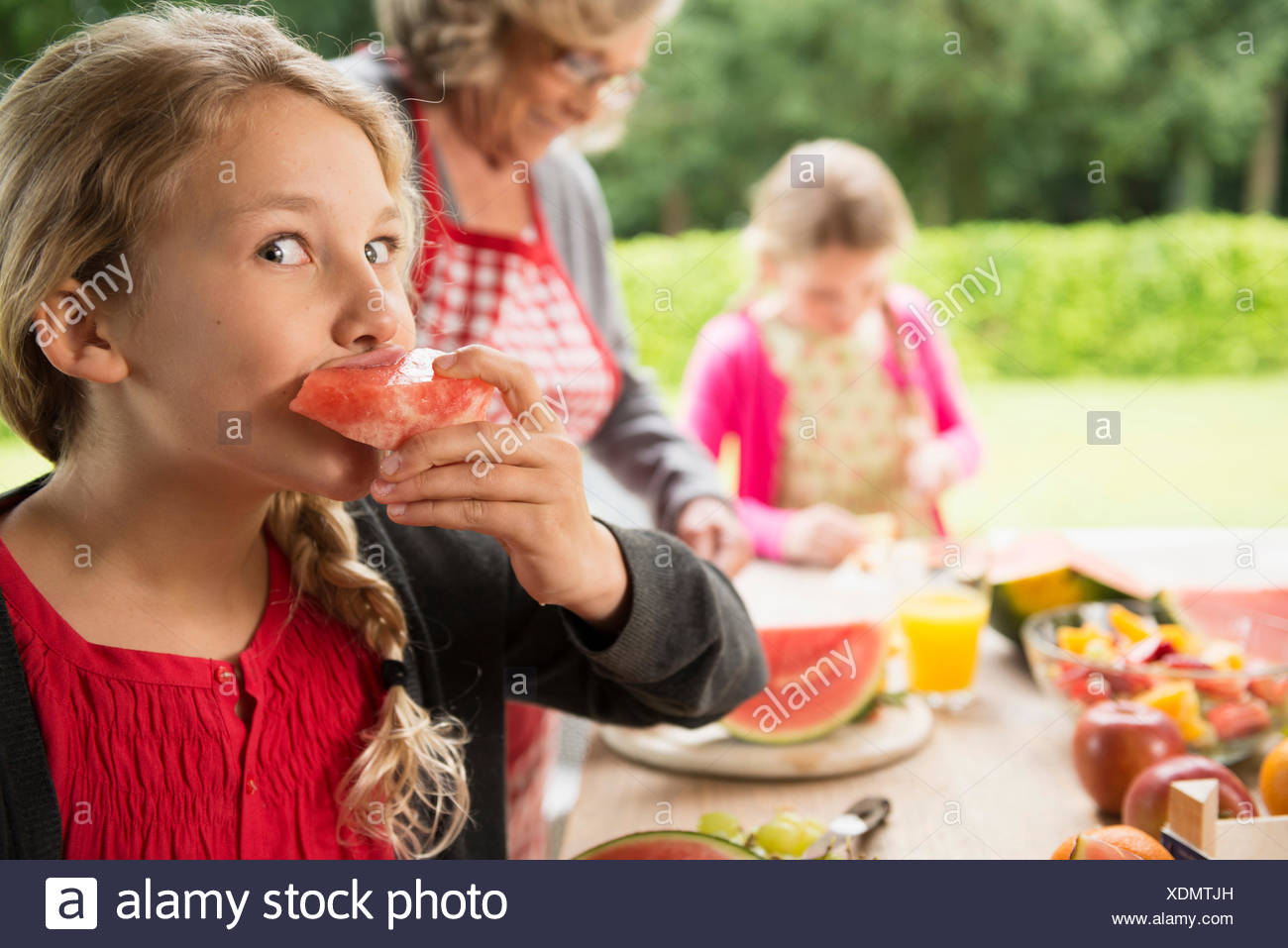 Mischievous girl at patio table eating watermelon slice - Stock Image
