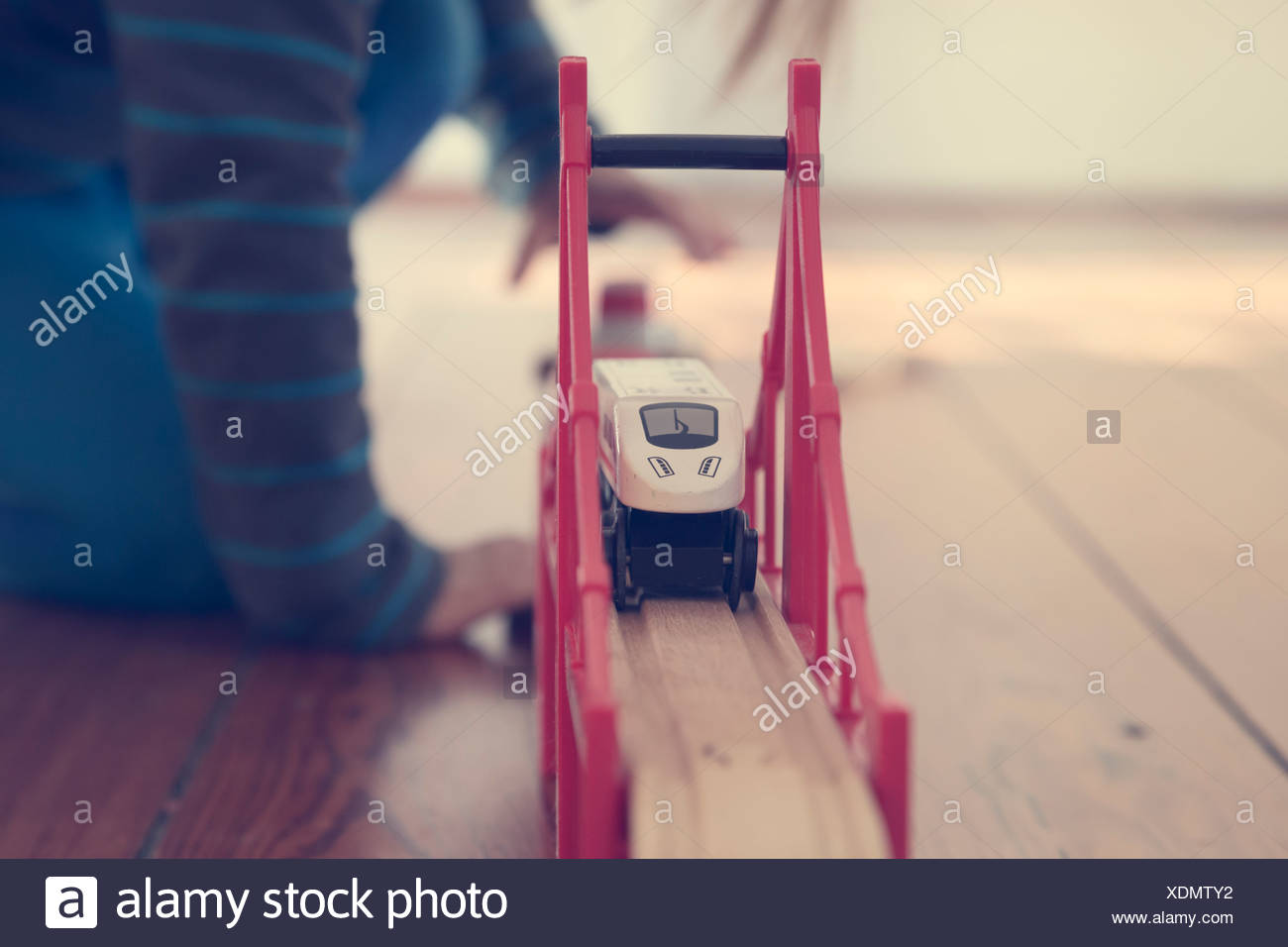 Little girl playing with wooden railroad, partial view - Stock Image