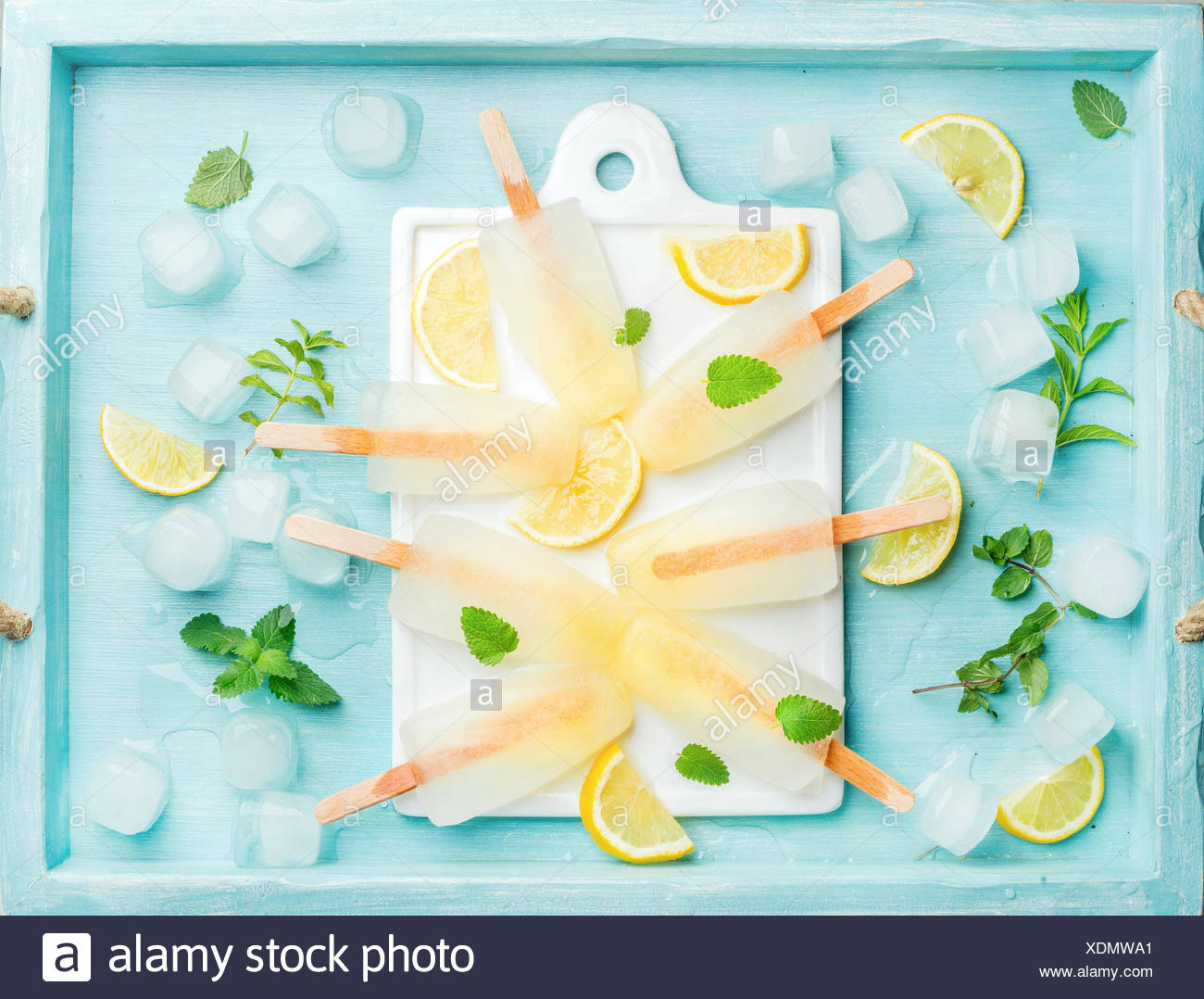 Lemon ice lollies on white ceramic board served with lemon slices, ice cubes and mint leaves over blue Turquoise backdrop, top v - Stock Image