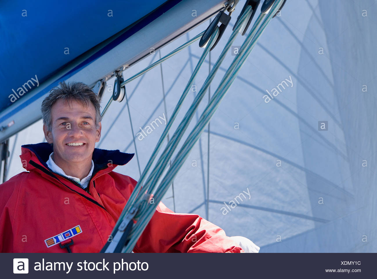 Man in red jacket sitting on deck of sailing boat below sail, smiling, portrait, low angle view - Stock Image