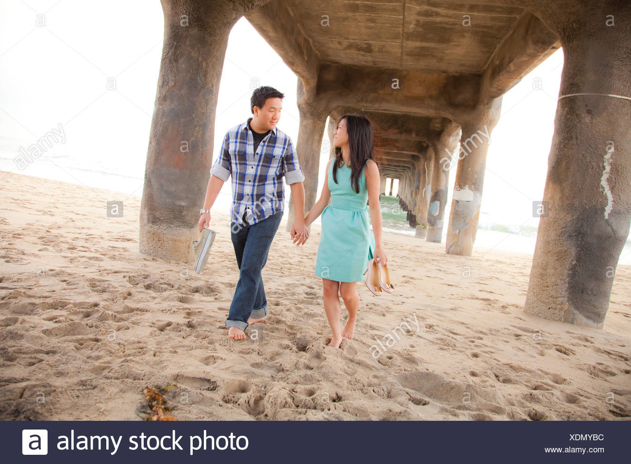 Couple holding hands, walking barefoot  under a pier - Stock Image