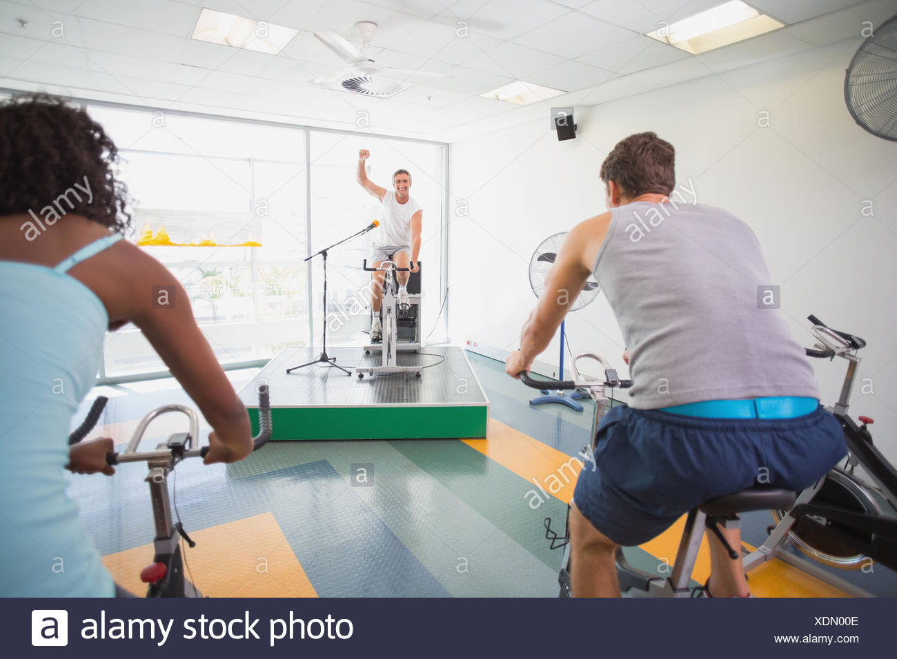 Spin class working out with motivational instructor - Stock Image