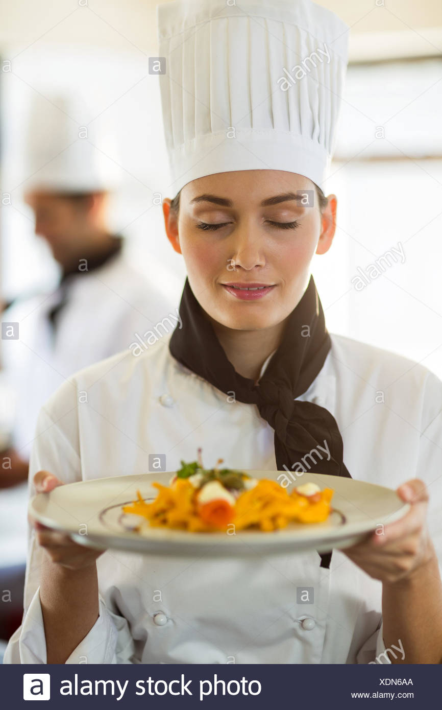 Close-up of head chef with eyes closed smelling food - Stock Image
