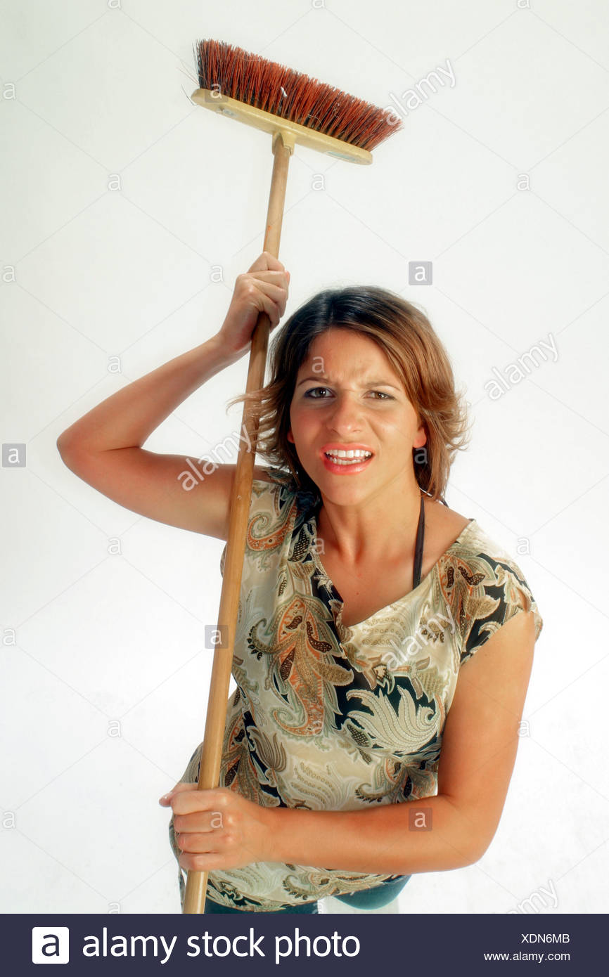 nerved woman with broom and mop - Stock Image