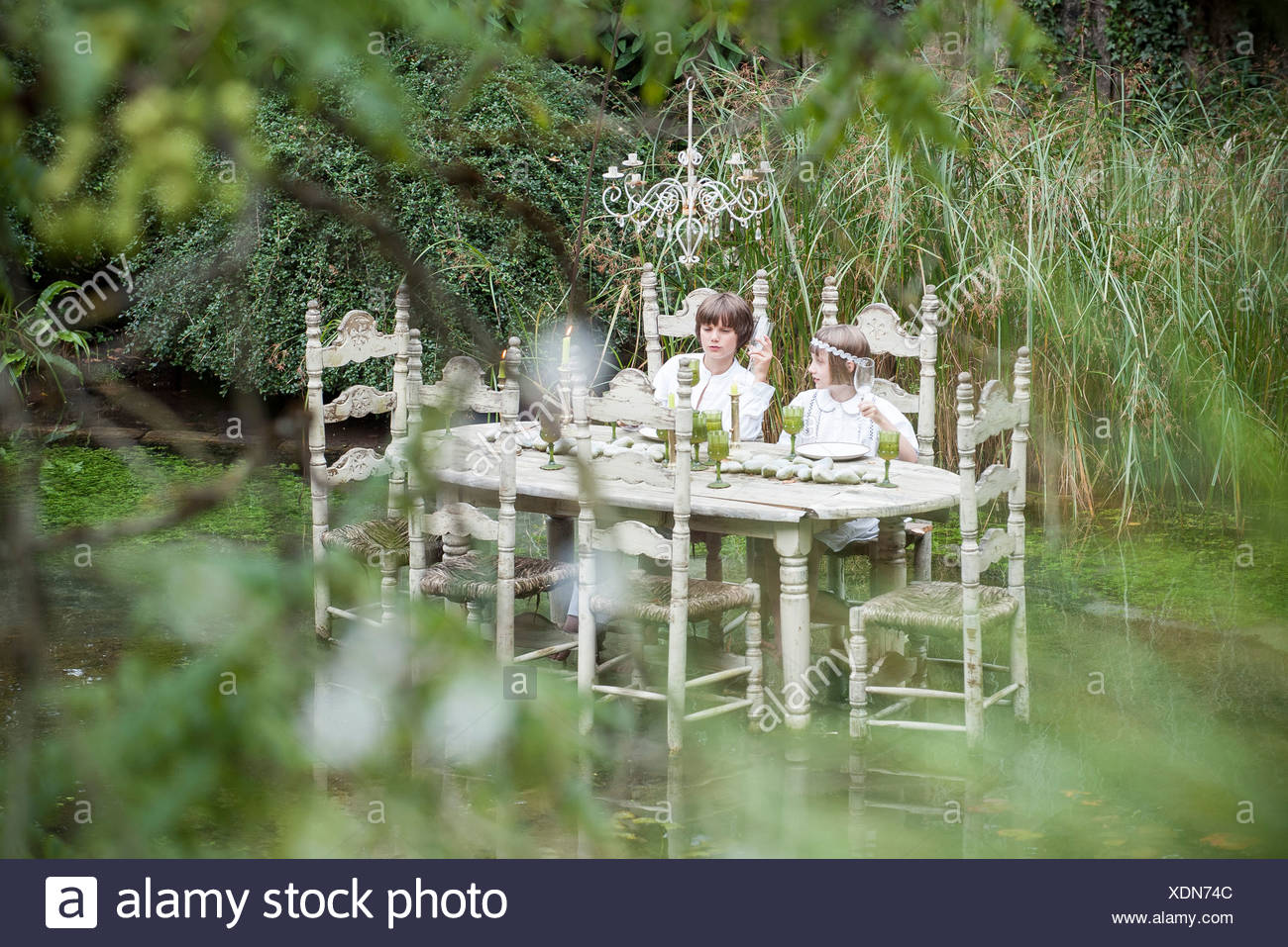 Children seated at dining table floating on lake - Stock Image