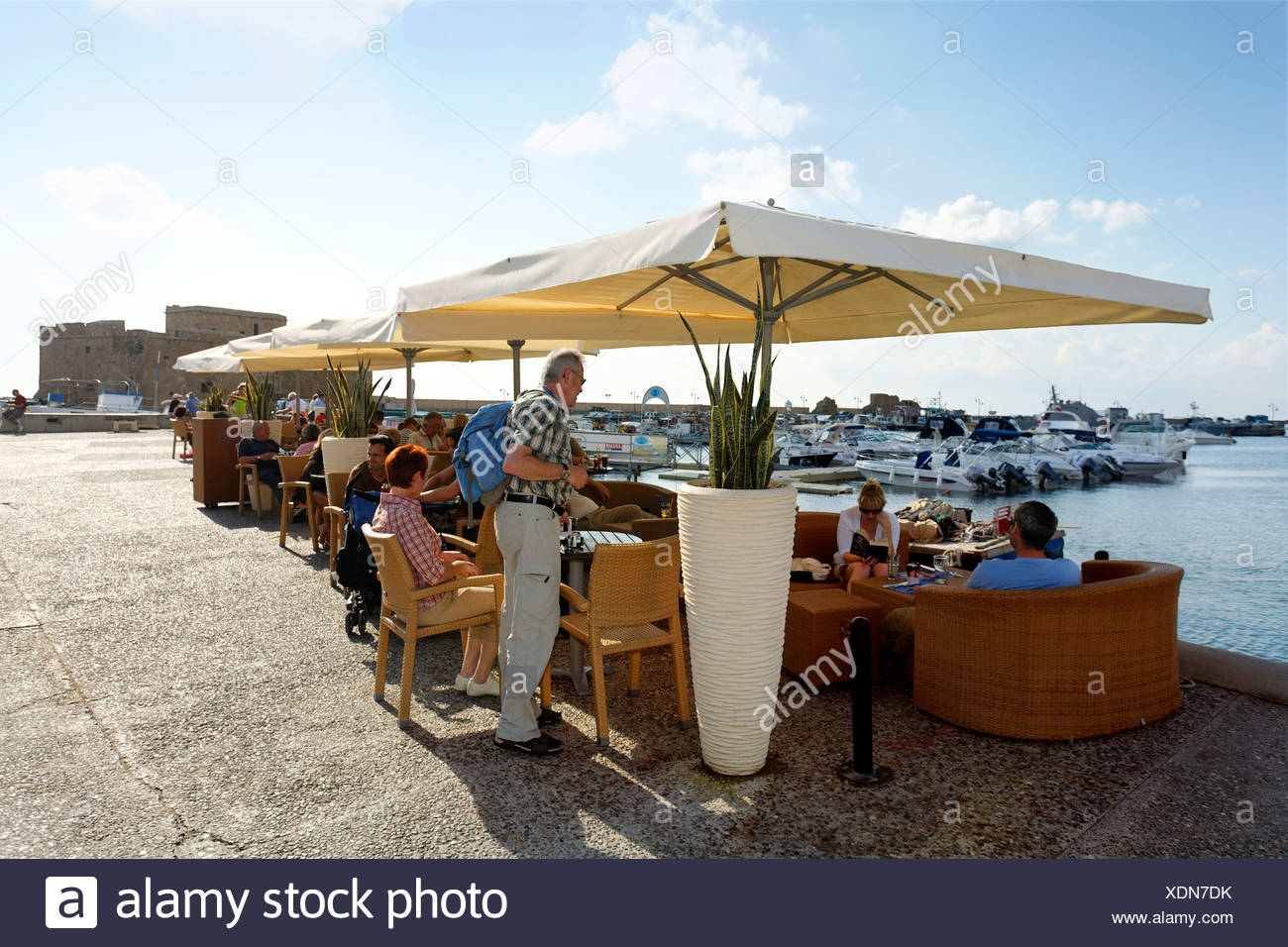 People in a cafe with sun umbrellas at the shore promenade, citadel, Paphos, Pafos, Cyprus, Europe Stock Photo