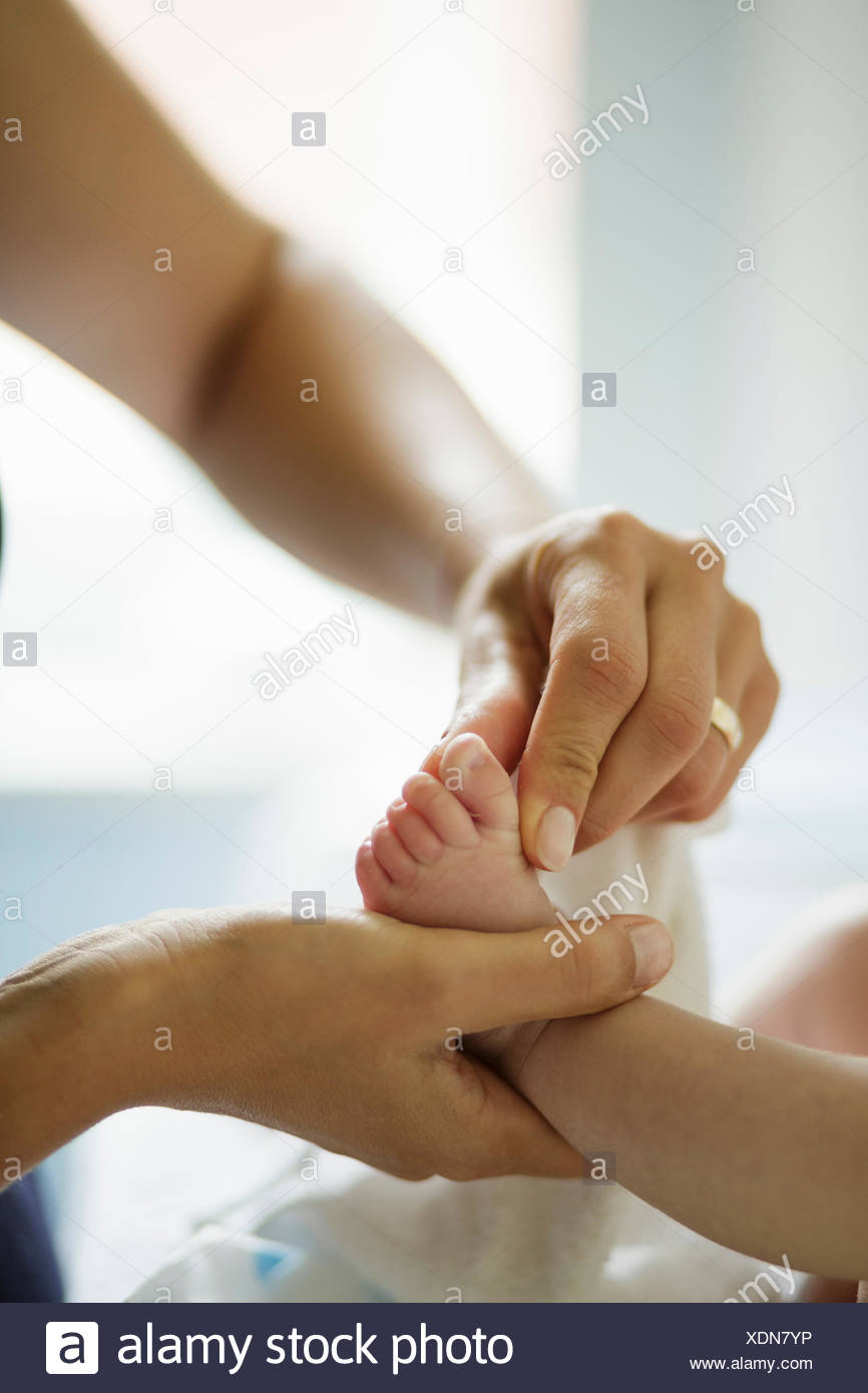 Close up of mothers hand cleaning baby sons feet Stock Photo