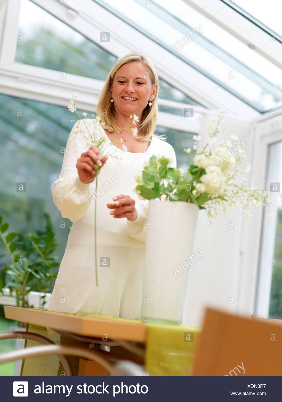 Woman arranging flowers in vase - Stock Image