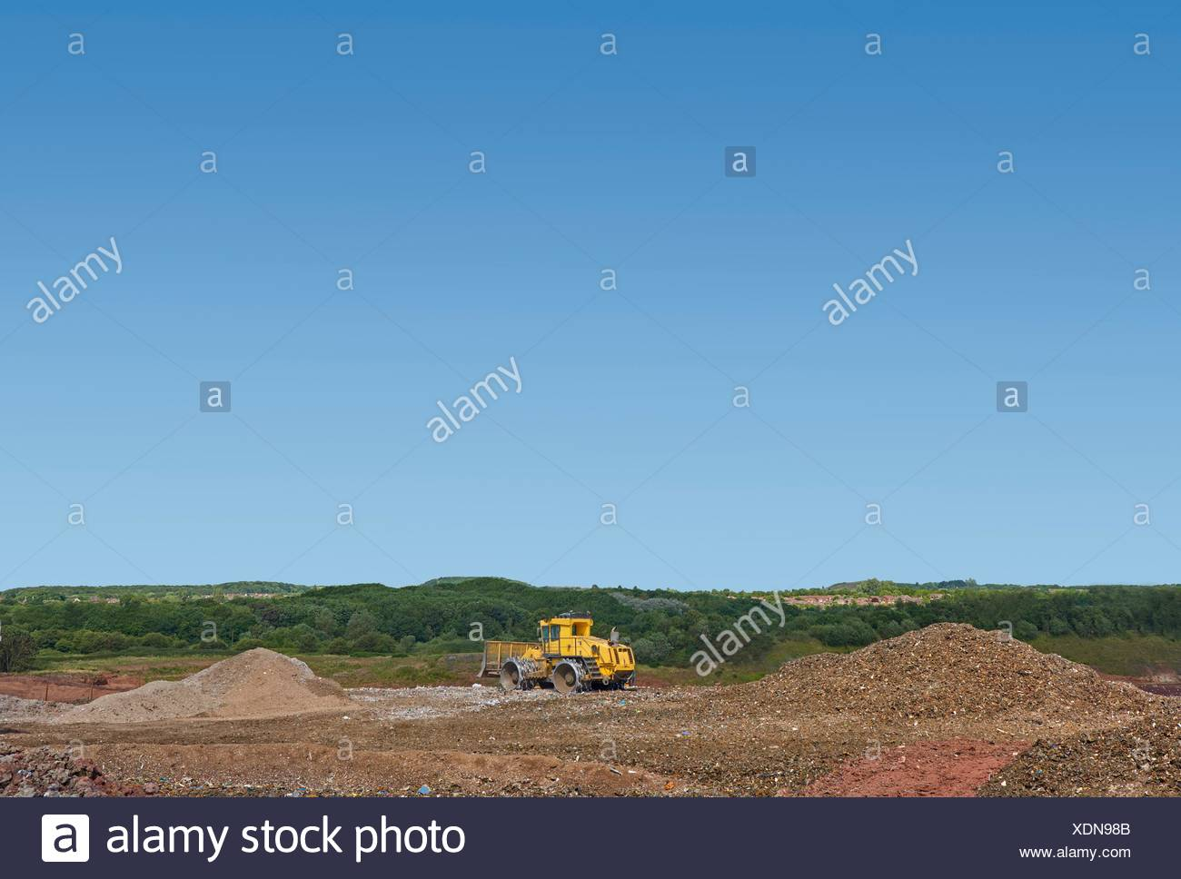 Digger burying waste on landfill site - Stock Image
