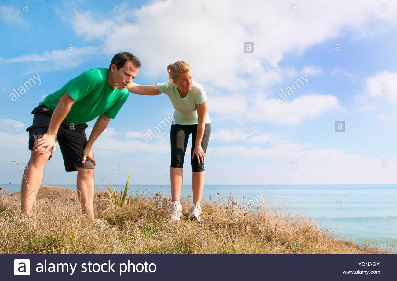 Mid adult couple taking a break from exercise, Thurlestone, Devon, UK - Stock Image