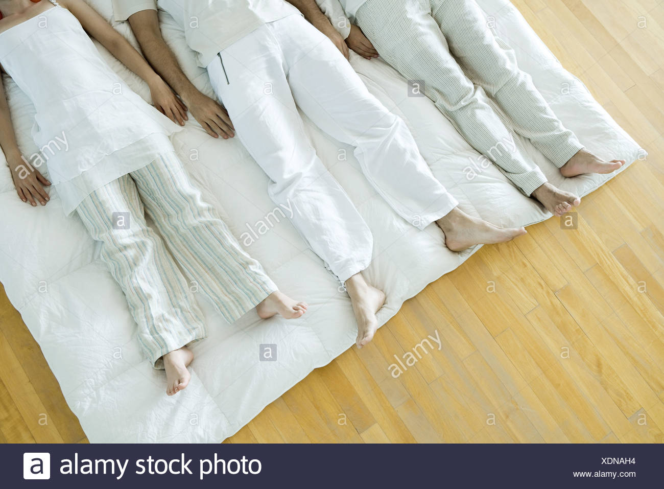 Group therapy, three adults lying side by side - Stock Image