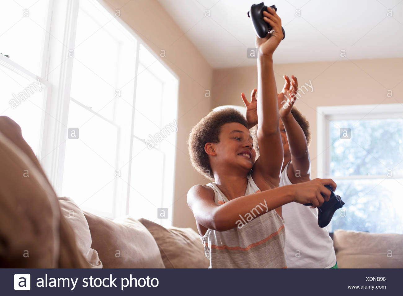 Two brothers playfighting over game controllers in living room - Stock Image