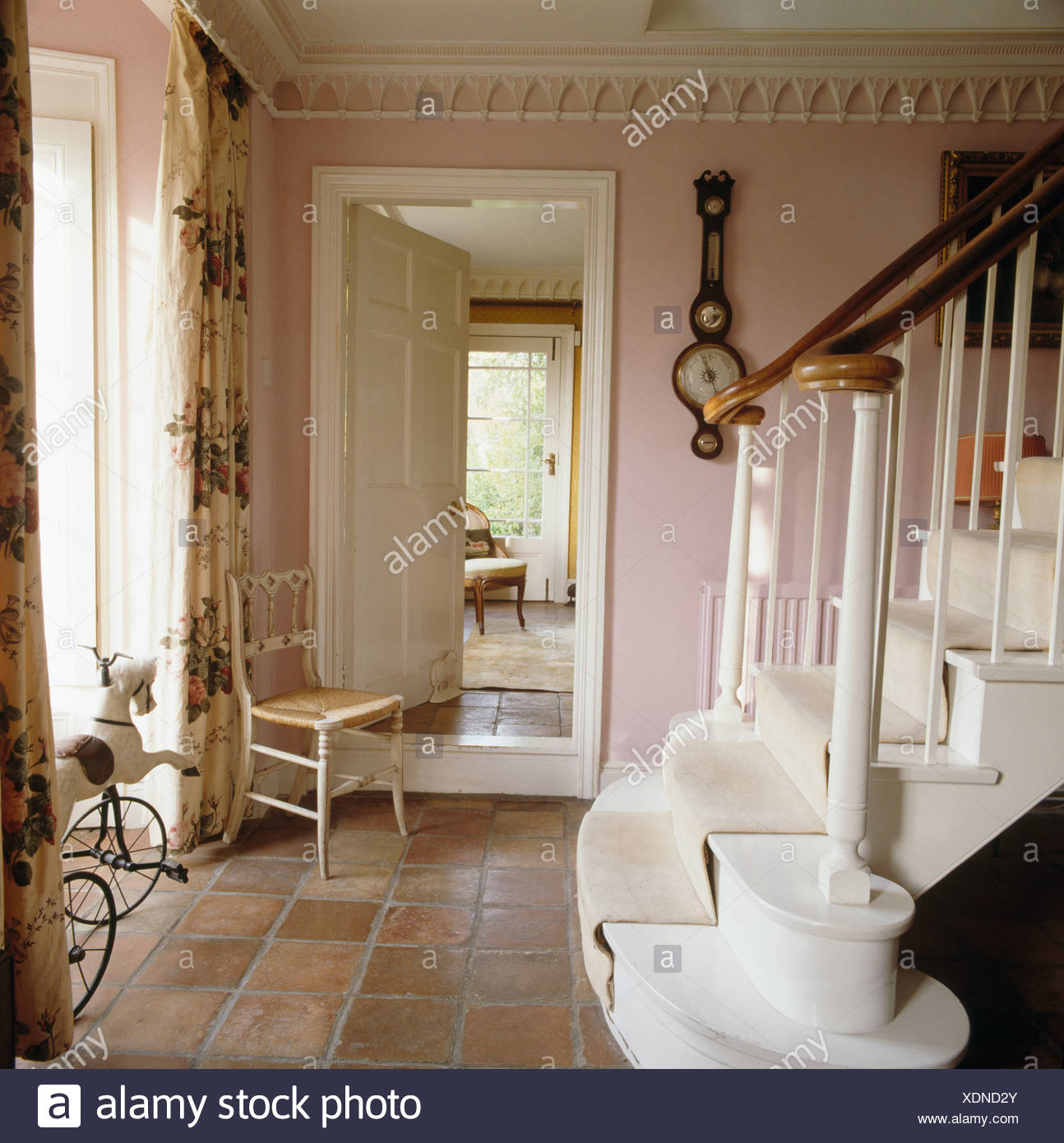 Old Stone Floor Tiles And Chair Beside Open Door To Dining Room In Pink Country Hall With Gothic Cornice White Staircase