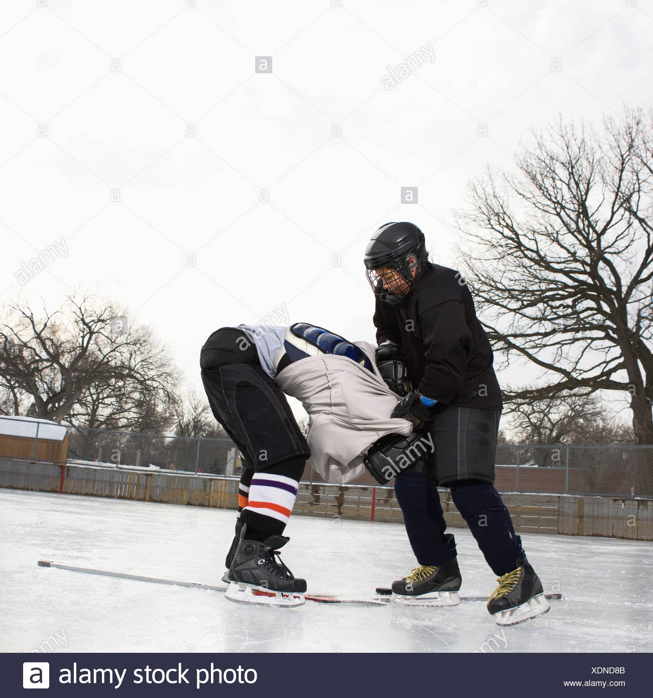 Ice hockey player boy roughing up another player on the ice rink - Stock Image