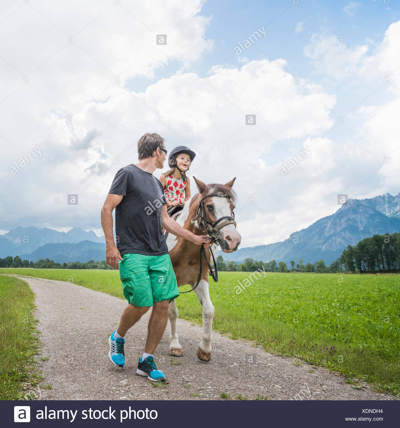 Father guiding daughter riding horse, Fuessen, Bavaria, Germany - Stock Image