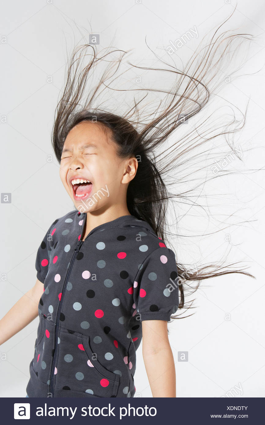 Young girl indoors shouting with hair flying back - Stock Image