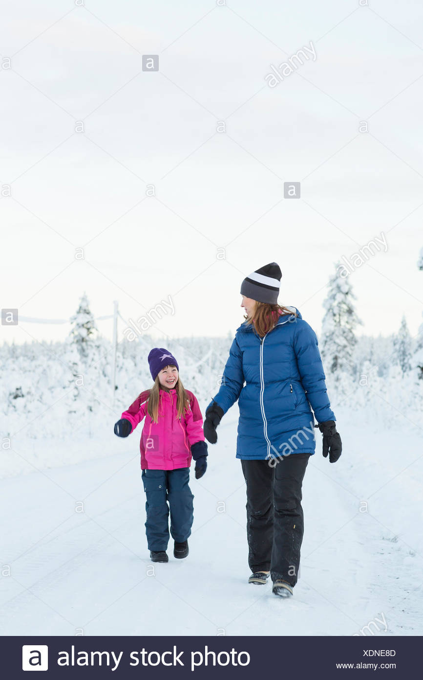 Sweden, Lapland, Gallivare, Girl (4-5) walking with mother along road in winter - Stock Image